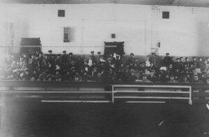Зрители в манеже смотрят на верховую езду офицеров бригады.
