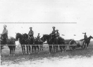Офицер с группой солдат в поле у орудийных повозок.