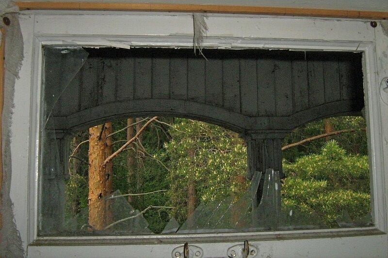 Сосновый лес сквозь разбитое окно с осколками стекла на втором этаже заброшенного дебаркадера