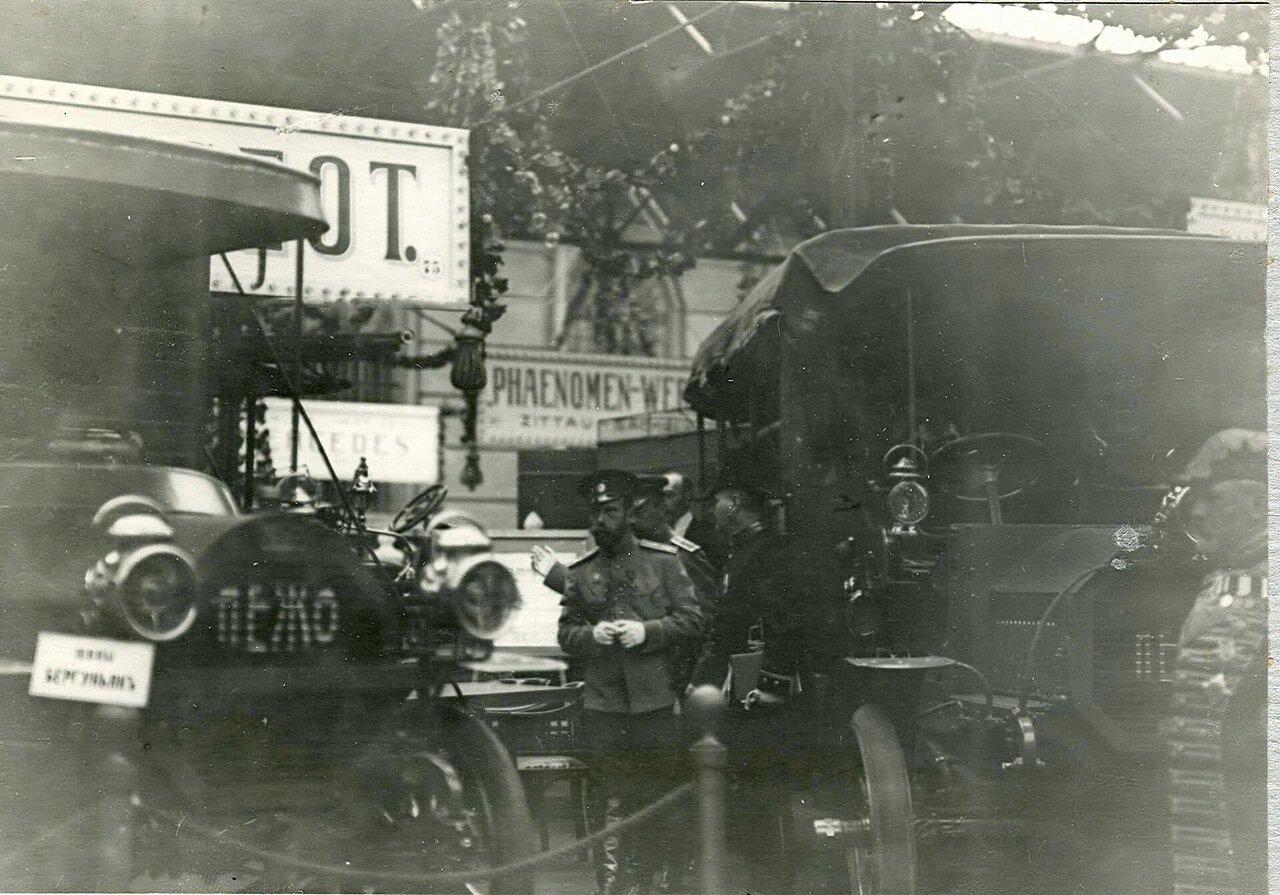 12. Император Николай II и сопровождающие его лица осматривают на выставке автомобили фирмы Пежо