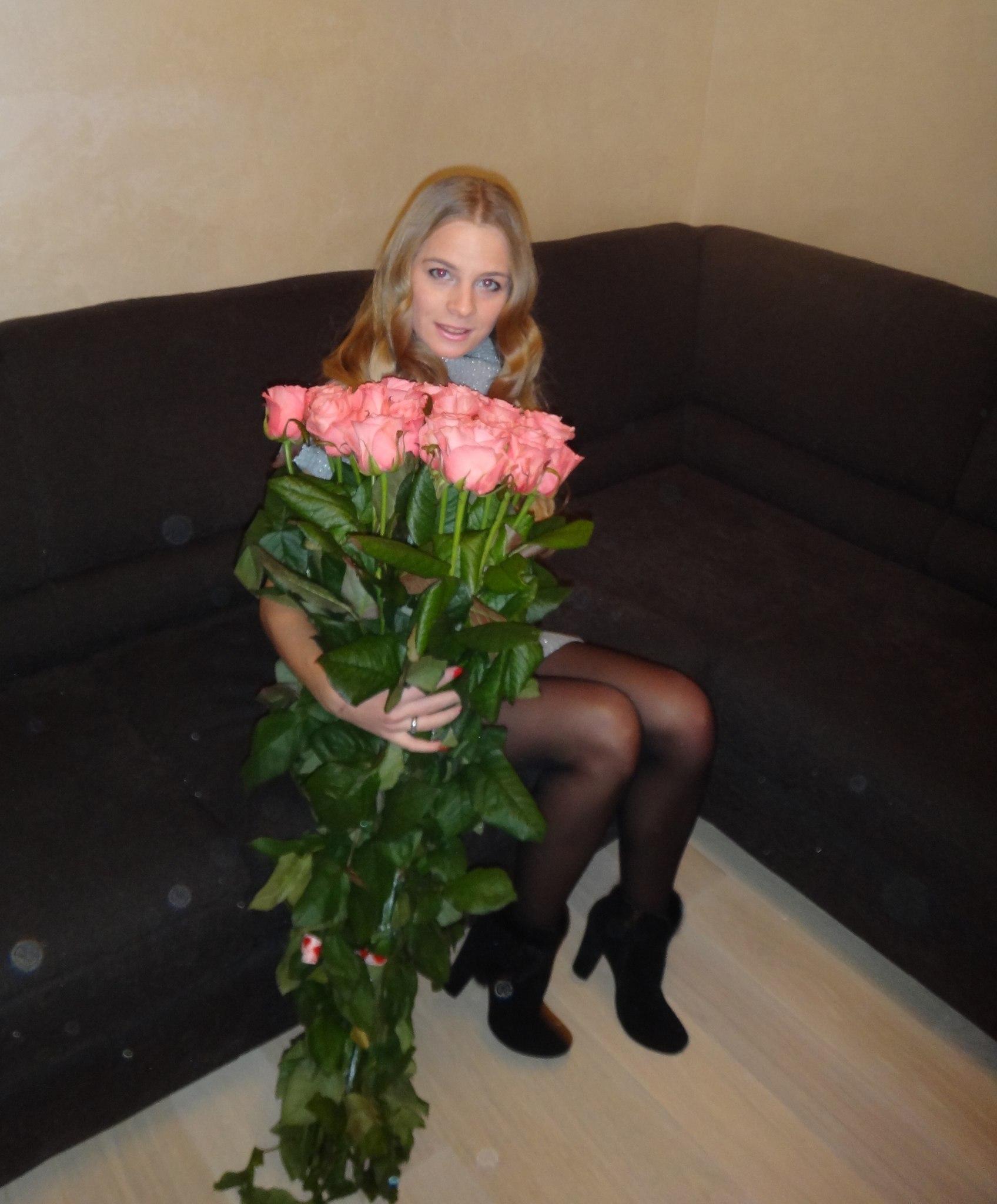 Красотка с большим букетом роз в голубой водолазке