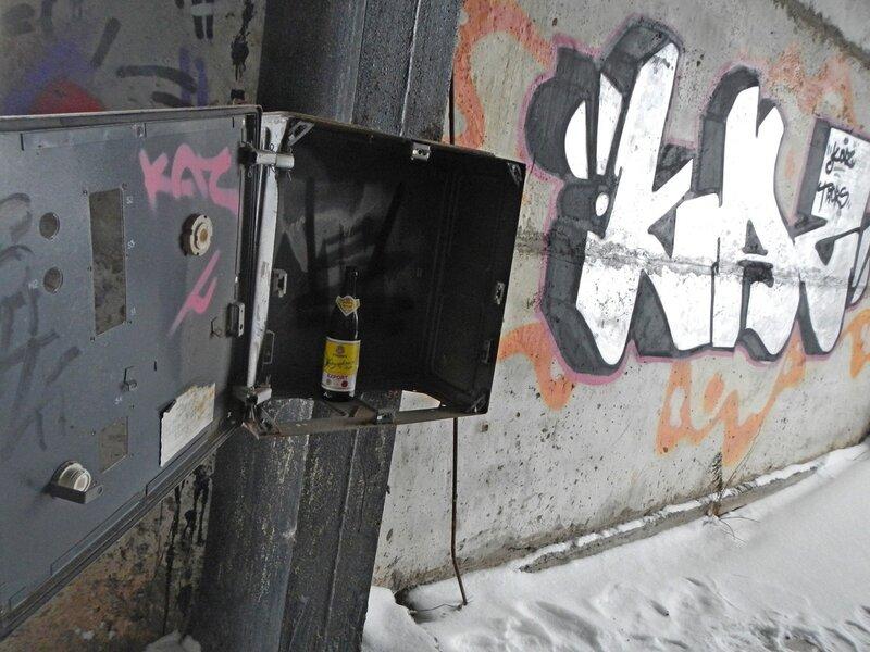 Раскуроченный электрощит с бутылкой пива и граффити на бетонной стене