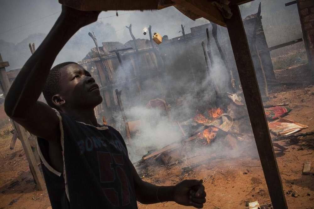 Мальчик-погромщик занимается поиском хоть какой-либо добычи среди остатков горящего жилища семьи бежавших мусульман