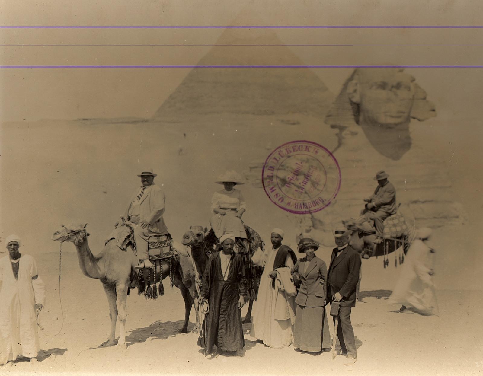 Гиза. Группа туристов с верблюдами и гидами перед Сфинкс и пирамидой