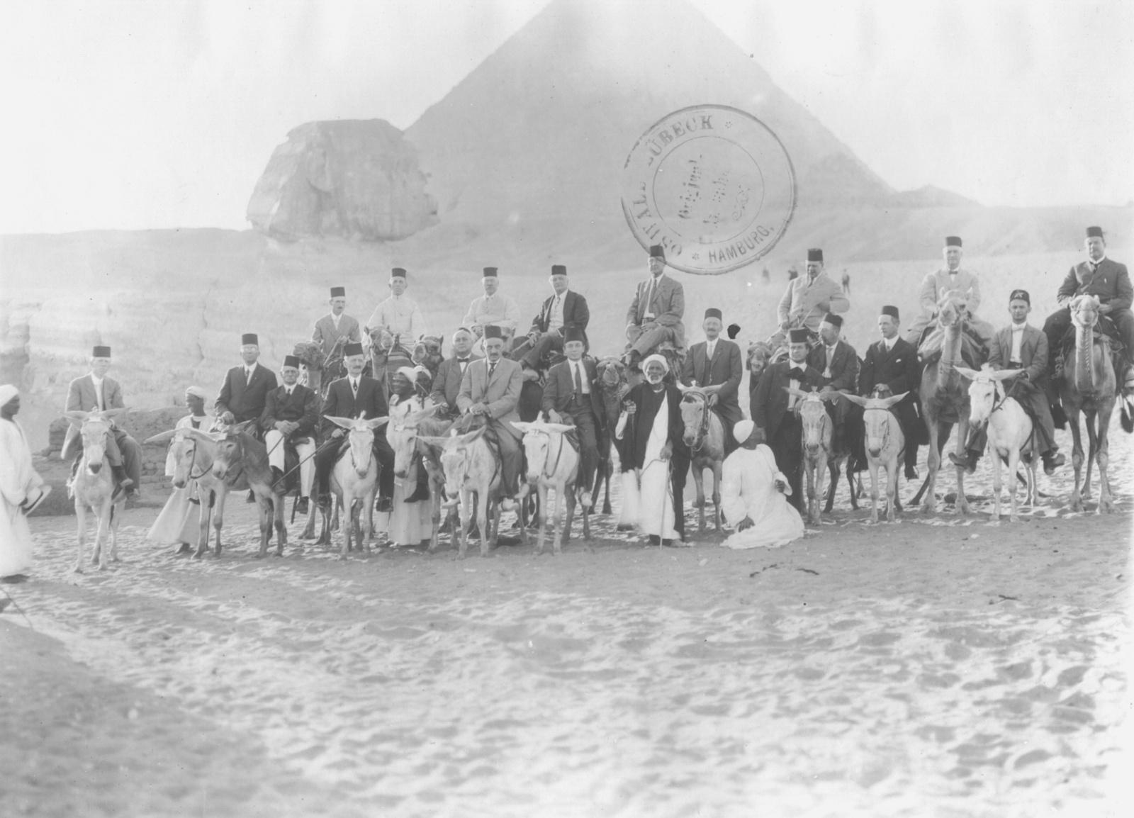 Гиза. Туристическая группа на верблюдах и ослах, позирует со своими проводниками перед Сфинксом