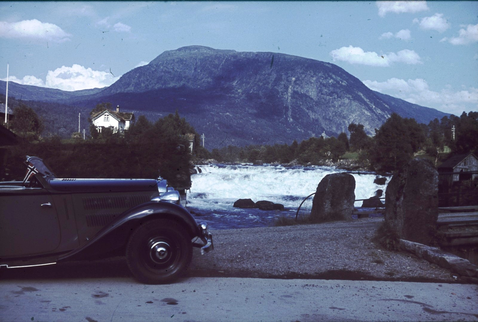 Припаркованная машина с норвежским флагом. Вид на горный хребет