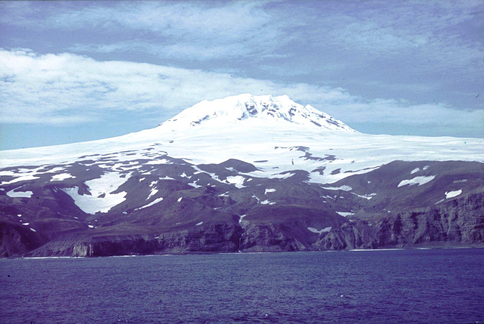 Скалистый берег со снежным массивом