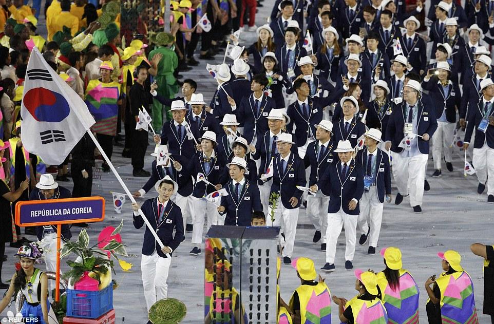 Южнокорейские спортсмены шествуют со своим флагом.