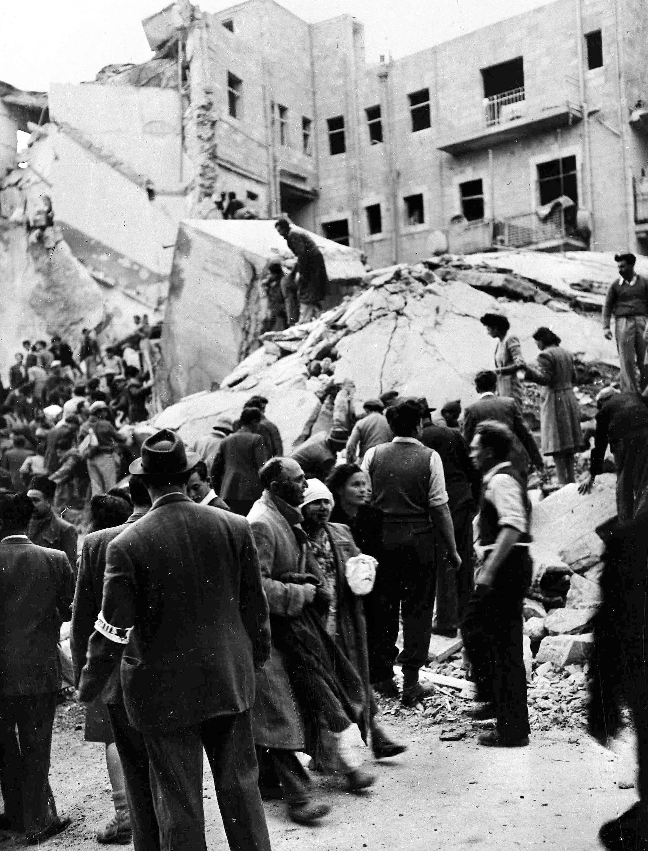 Пострадавшая еврейская пара проходит мимо спасателей, которые ищут раненых и мертвых людей в обломках магазинов на улице Бен Иегуда, Иерусалим, после того, как взорвалась бомба. Бомба убила 52 еврея и ранила еще 100. 22 февраля