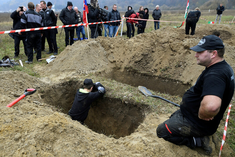 Gravediggers rest after competing in a grave digging championship in Trencin, Slovakia