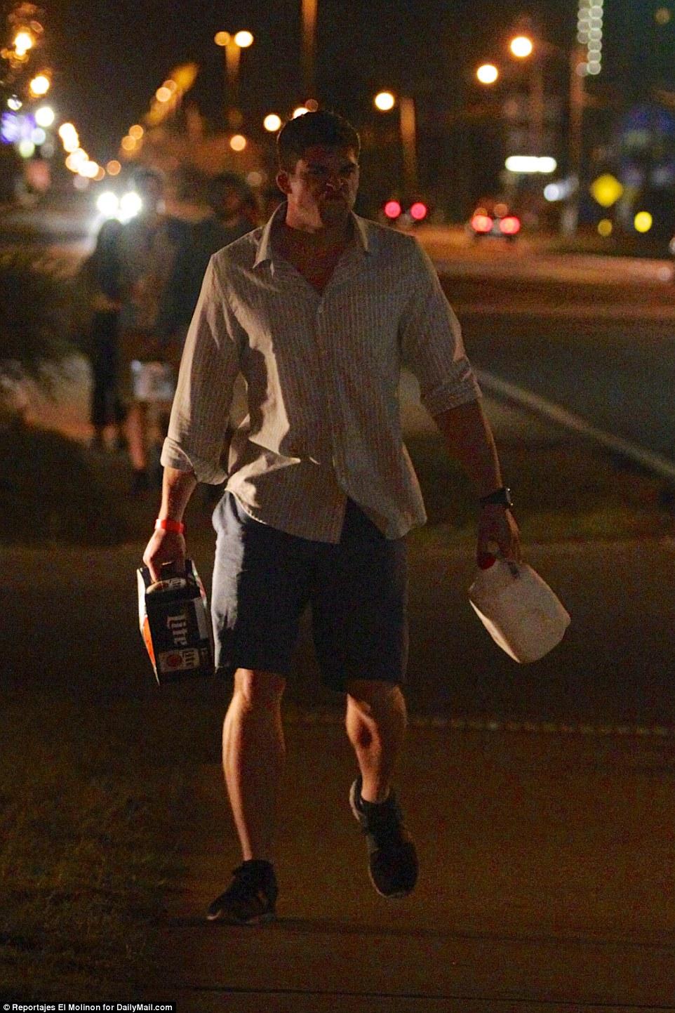 Парень отправляется домой с шестью бутылками пива и пакетом молока.