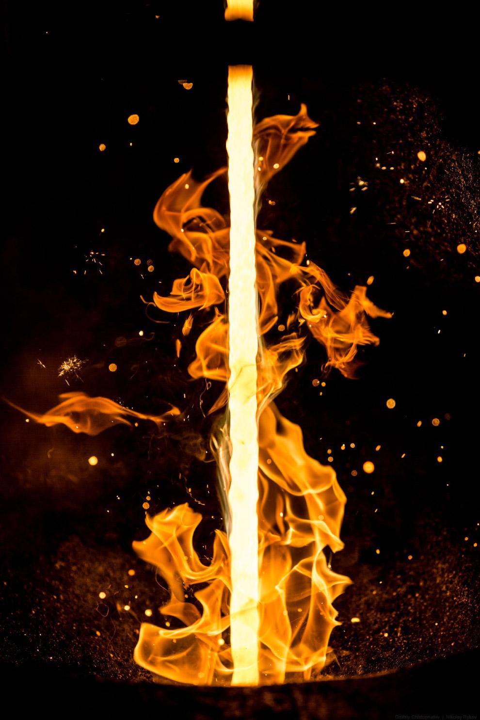 Бесконечные металлические слитки плавно вытекают из кристаллизатора и разрезаются газовой кисло