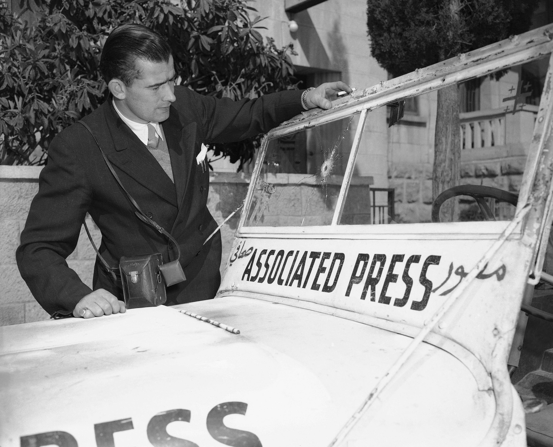 Джим Прингл смотрит на отверстие на ветровом стекле джипа Associated Press, вызванное арабской пулей во время боевых действий в еврейском квартале Иерусалима.  23 февраля,