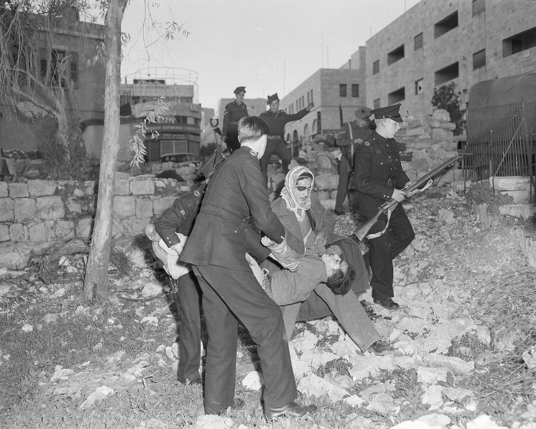 Умирающего еврейского водителя несут полицейский и араб с мусульманского кладбища на улице Мамила, Иерусалим, после подрыва бронированной машины. 7 января
